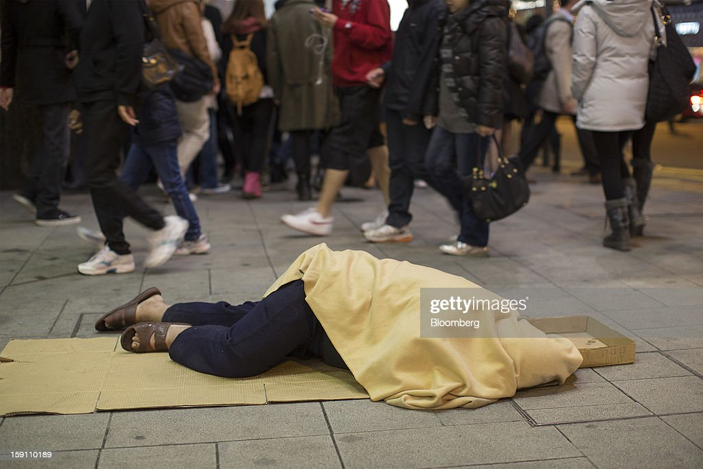 A person lies on a sidewalk as pedestrians walk past in Hong Kong, China, on Friday, Jan. 4, 2013. Chief Executive Leung Chun-ying, who has been buffeted by student protests and low popularity since taking office on July 1, has pledged to tackle Asia's biggest wealth gap as the division between poor and rich widened to its worst level since at least 1971. Photographer: Jerome Favre/Bloomberg via Getty Images