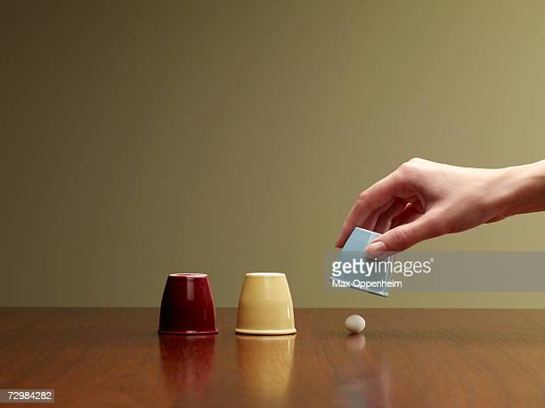 Person lifting third cup over ball