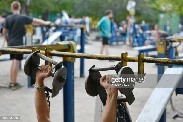 A person lifts dumbbells on August 18 2017 at an open air gym in Ukraine's capital Kiev Foundedin the 1970s the busy open air gym called Kachalka in...