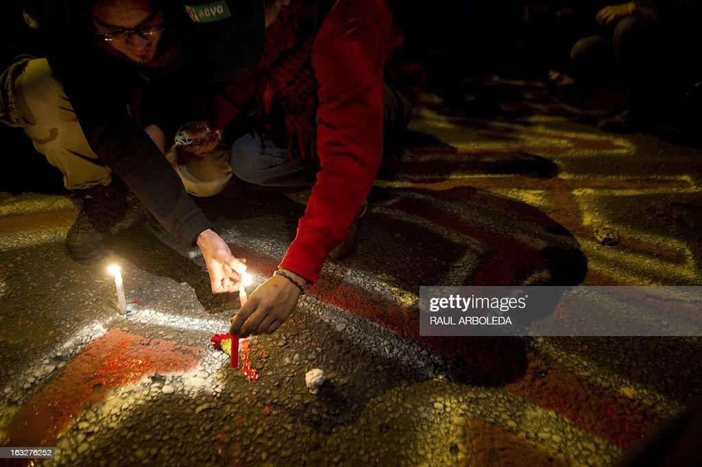 A person lights a candle outside the Venezuelan embassy in Bogota, Colombia on March 6, 2013, after Venezuelan President Hugo Chavez's death. The flag-draped coffin of Venezuelan leader Hugo Chavez was borne through throngs of weeping supporters on Wednesday as a nation bade farewell to the firebrand leftist who led them for 14 years. AFP PHOTO / Raul ARBOLEDA