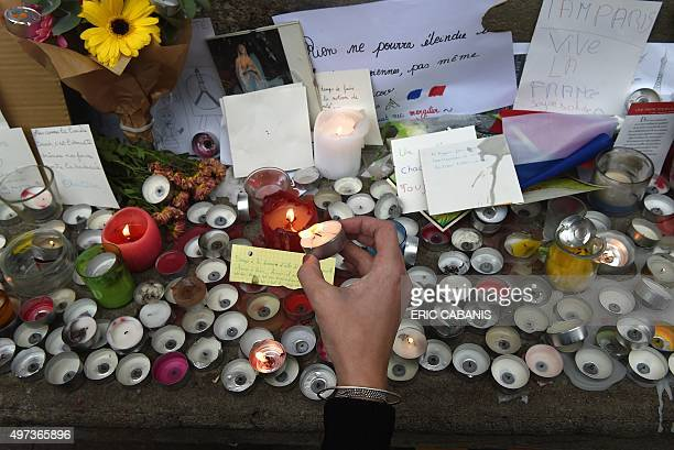 A person lights a candle within a minute of silence on November 16 2015 on the Place du Capitole in Toulouse to pay tribute to victims of the attacks...