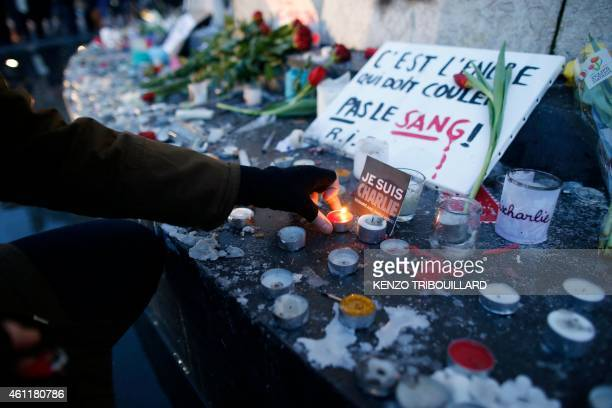 A person lights a candles next to a placard reading 'Ink must flow not blood RIP' during a vigil held on the Place de Republique in Paris on January...