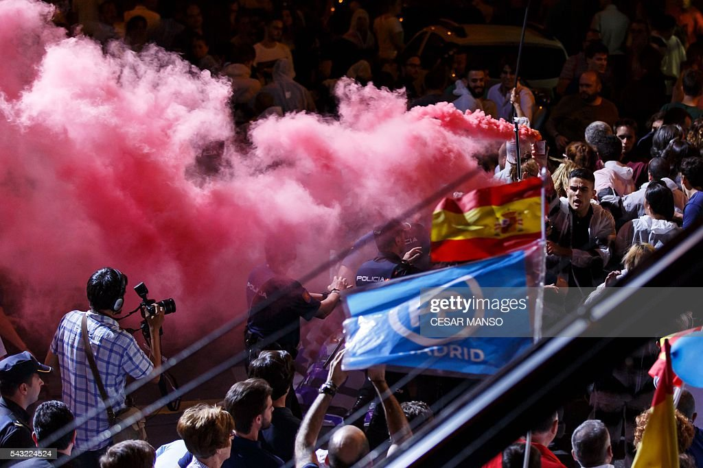 A person lights a flare in front of the PP headquarters during Spain's general election in Madrid on June 26, 2016. Spain's repeat polls ended on June 26 with the incumbent conservatives appearing to have scored a small win tailed closely by a far-left coalition led by Podemos, exit polls said, against a backdrop of record/low abstention. / AFP / CESAR