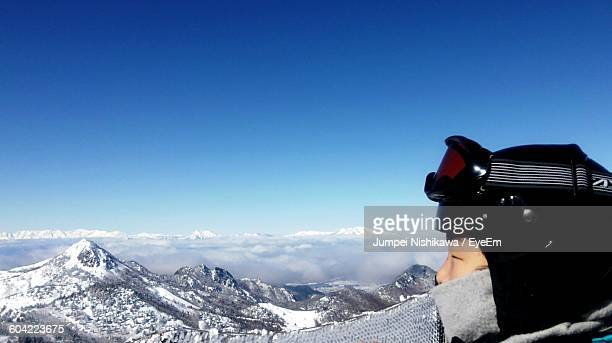 Person Looking At Mountain While Hiking Against Sky