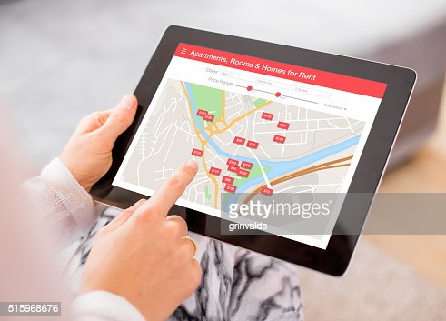 Person looking for places to stay on digital tablet app : Stock Photo