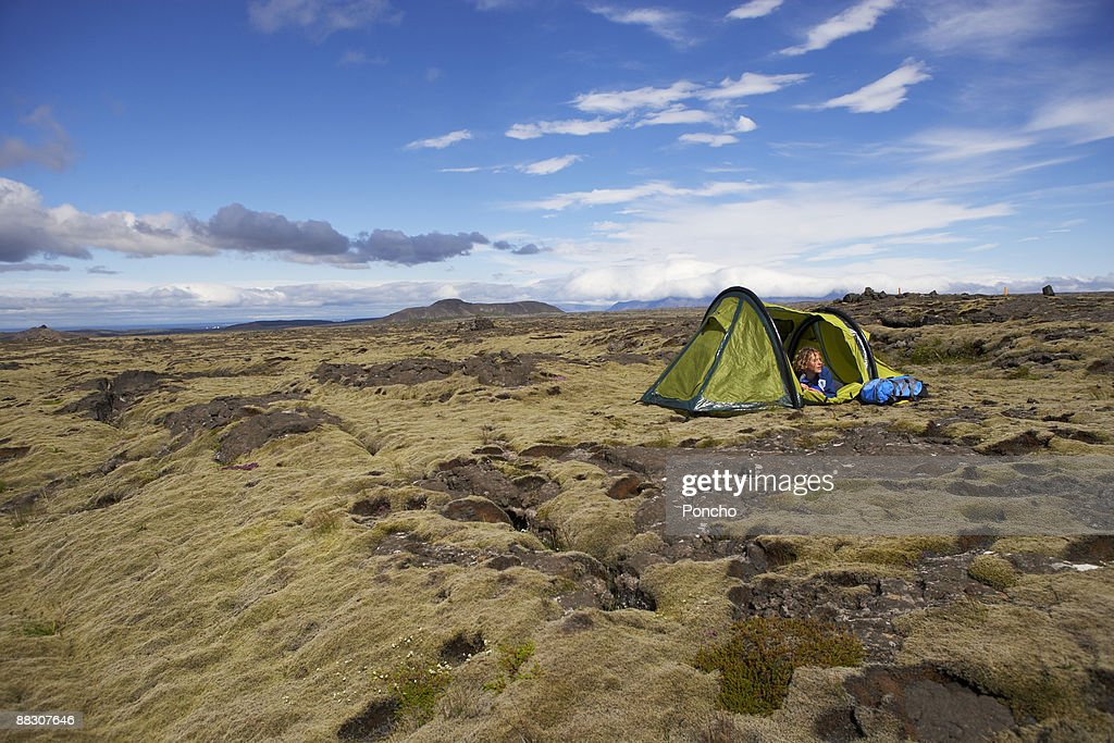 Person looking out of tent : Stock Photo