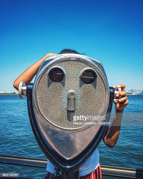 Person Looking Through Coin-Operated Binoculars By Sea At Liberty Island