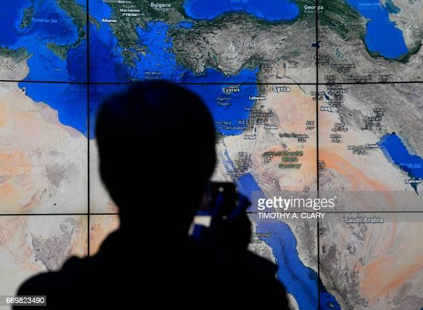 A person looks at a Google Earth map of the Mideast on a screen as Google Earth unveils the revamped version of the application April 18 2017 at a...