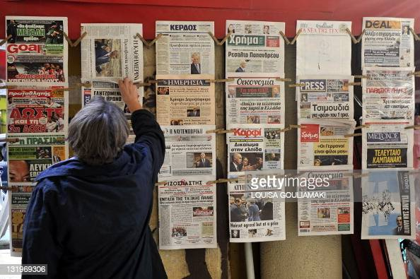 A person looks at a newspaper in Athens on November 1 2011 Greek Prime Minister George Papandreou plunged the euro and stock markets back into crisis...