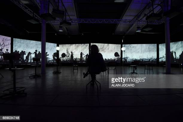A person looks at a piece of art by South African artist William Kentridge called 'more sweetly play the dance' as part of the exhibition Afriques...