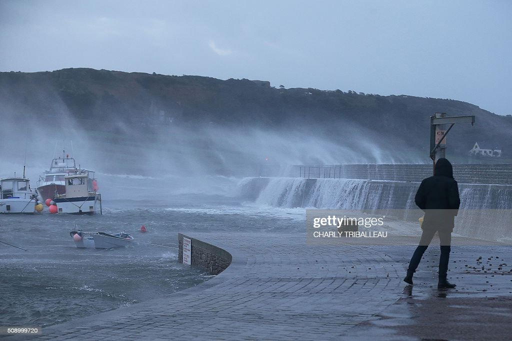 A person looks at anchored boat in a harbour in Auderville, northwestern France, on February 8, 2016, as strong winds hit the region. Winds of over 130 kh/h were recorded in the region where 16 departments have been placed under alert for for wind and flooding waves. / AFP / CHARLY TRIBALLEAU