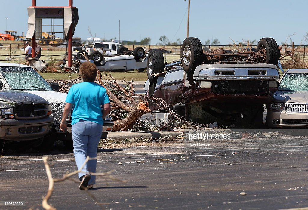 A person looks at cars damaged by a powerful tornado on June 1, 2013 in El Reno, Oklahoma. The tornado ripped through the area killing at least 9 people and injuring many and destroyed homes and buildings.
