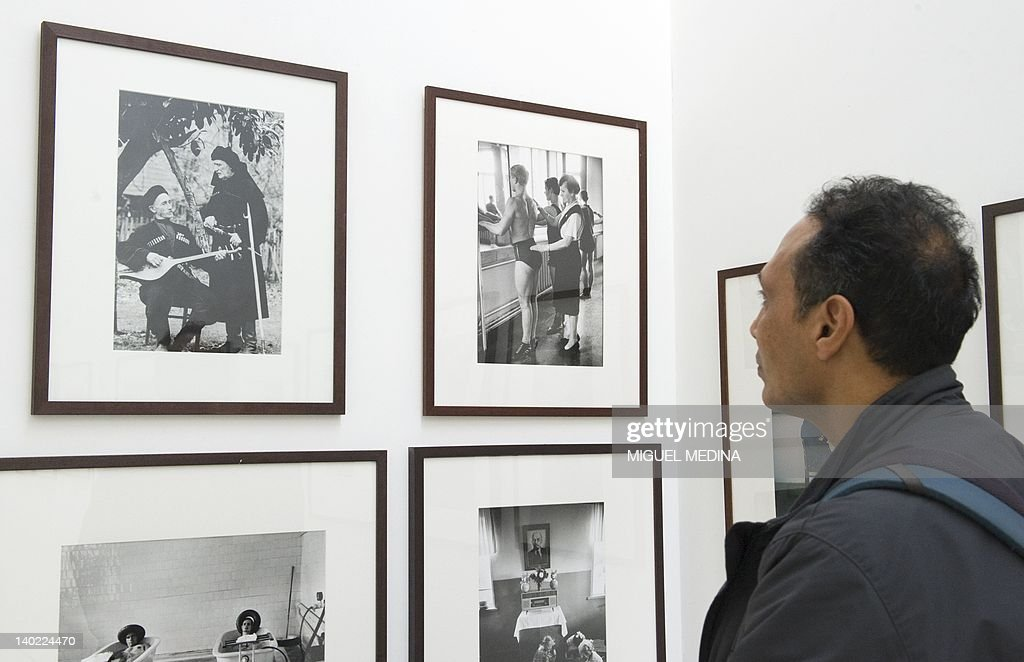 A person looks at photographs on display during an exhibition entitled 'All About Eve' at the Arts Sensus Gallery in central London on March 1, 2012. Eve Arnold, a US photographer who took famous pictures of Marilyn Monroe among other renowned figures and was a pioneering member of the Magnum photo agency died on January 5 at the age of 99. Arnold was the first female photographer to become a full member of the storied Magnum agency in 1957. Her pictures of figures such as Monroe, Malcolm X and Marlene Dietrich were famous.