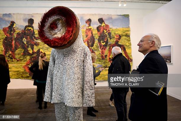 A person looks at 'Soundsuit' by Nick Cave during the VIP opening of The Armory Show 2016 in New York March 2 2016 / AFP / Timothy A CLARY /...