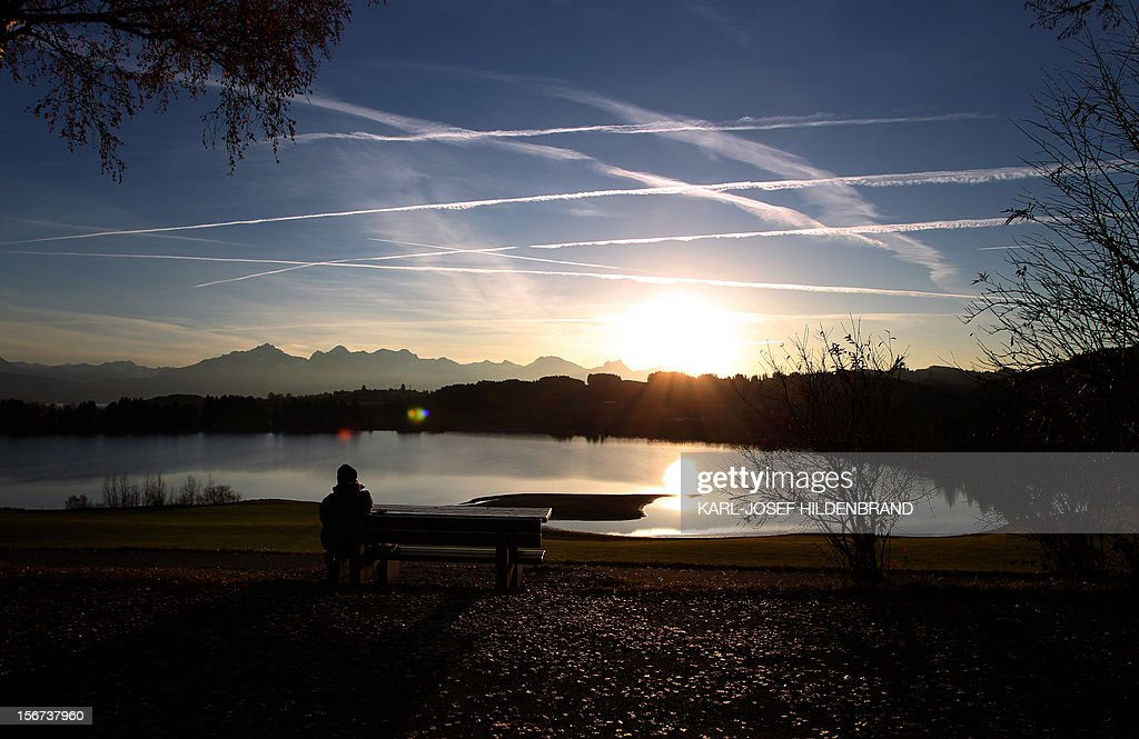 A person looks at sunset on November 19, 2012on the shore of Forggen lake in Roshaupten, southern Germany. AFP PHOTO/ Karl-Josef Hildenbrand/GERMANY OUT