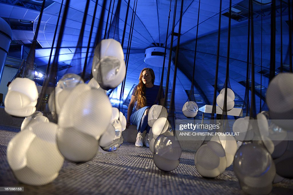 A person looks at the art creation 'PIP Show' by French artist Camille Lorin made with fishnet stockings containing breast implants from the Poly Implant Prothèse (PIP) company on April 19, 2013 at La piscine de Frais-Vallon in Marseille, southern France, during an exhibition presented as part of the Marseille-Provence European Capital of Culture event. The trial of five executives of breast implant company PIP, including its founder Jean-Claude Mas, opened in the French city of Marseille on April 17, 2013. AFP PHOTO / ANNE-CHRISTINE POUJOULAT CAPTION