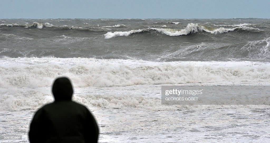 A person looks at waves at the Lacanau beach, western France, on February 9, 2016. France's Atlantic coast was lashed by powerful waves and authorities in resorts such as Biarritz took hasty measures to try to prevent the sea reaching the town. High winds buffeted northwestern Europe on February 8, leaving one woman in France in a coma after she was hit by an advertising hoarding. GOBET