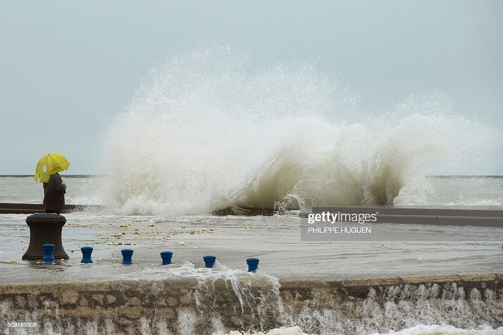 A person looks at waves breaking against the Wimereux breakwater, northern France, on February 9, 2016. High winds buffeted northwestern Europe on February 8, leaving one woman in France in a coma after she was hit by an advertising hoarding. Electricity was cut to 5,000 homes in northern France. / AFP / PHILIPPE HUGUEN