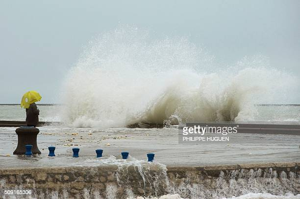 A person looks at waves breaking against the Wimereux breakwater northern France on February 9 2016 High winds buffeted northwestern Europe on...