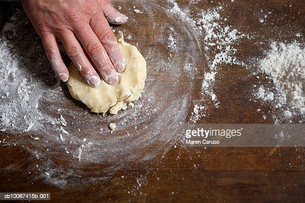 Person making dough on wooden board, close-up of hand