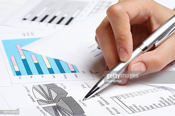 A person marking a pie chart on paper