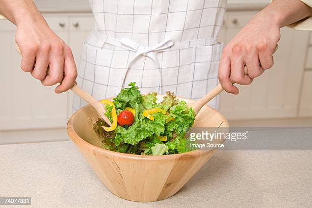 Person mixing salad