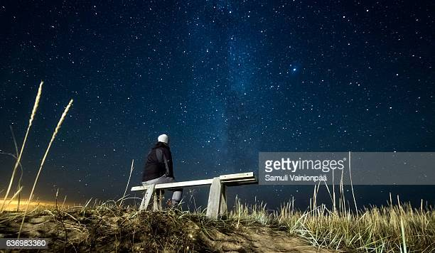 A person on a bench watching our galaxy, the Milky Way
