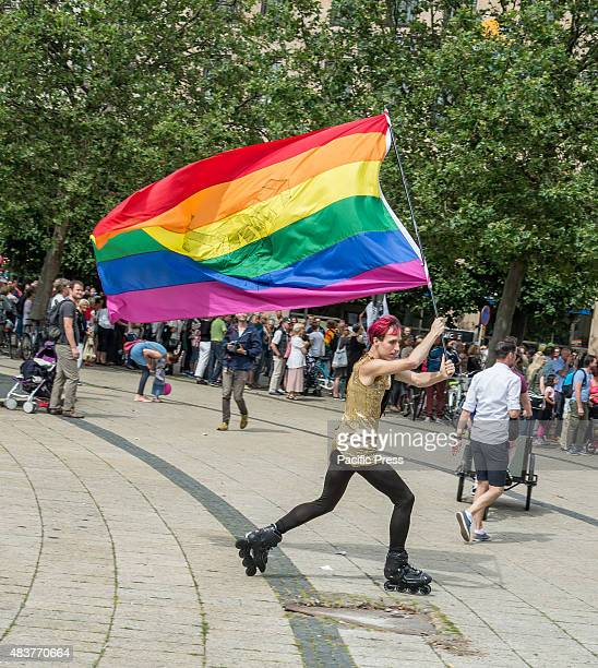 Person on roller blades waving the rainbow flag on Stortorget Parade closing the Rainbow festival Malmö Pride 2015 After a week long Pride festival a...