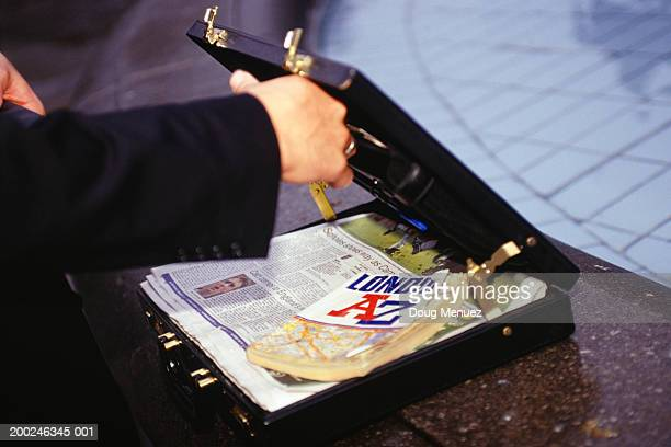 Person opening briefcase containing guidebook and newspaper