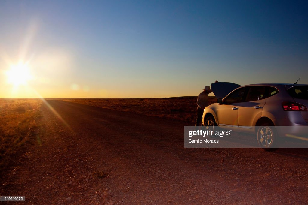 Person opening hood of car on remote road, Grand Canyon National Park, Arizona, United States