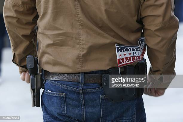 A person openly carrying a hand gun is pictured as people gather on the steps of the state capitol to protest Gov Jay Inslee's welcoming of all...