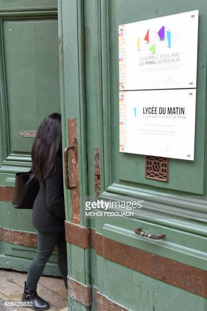 A person opens the door next to a sign reading 'Morning High School' in Le Mirail High School in Bordeaux southwestern France on March 20 2017 This...