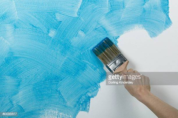Person painting glaze onto wall with brush