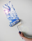 Person painting sky on wall with paint roller (Digital Composite)