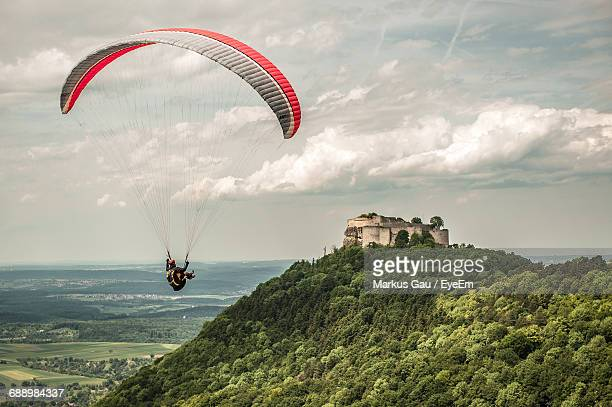 Person Paragliding By Swabian Jura Against Cloudy Sky