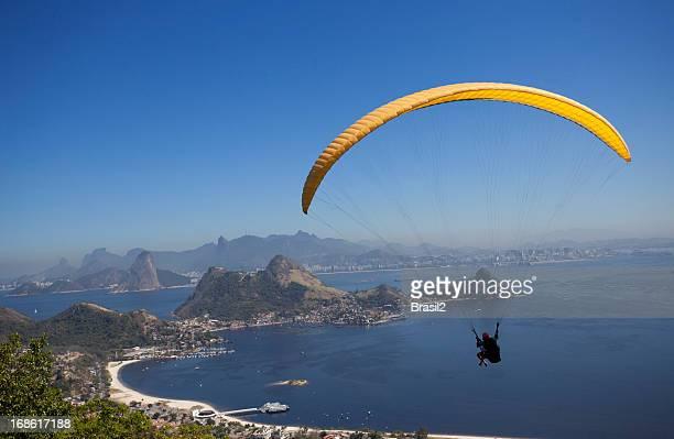 A person paragliding over calm blue sea in Rio de Janeiro