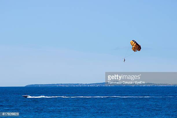 Person Parasailing Over Sea Against Sky