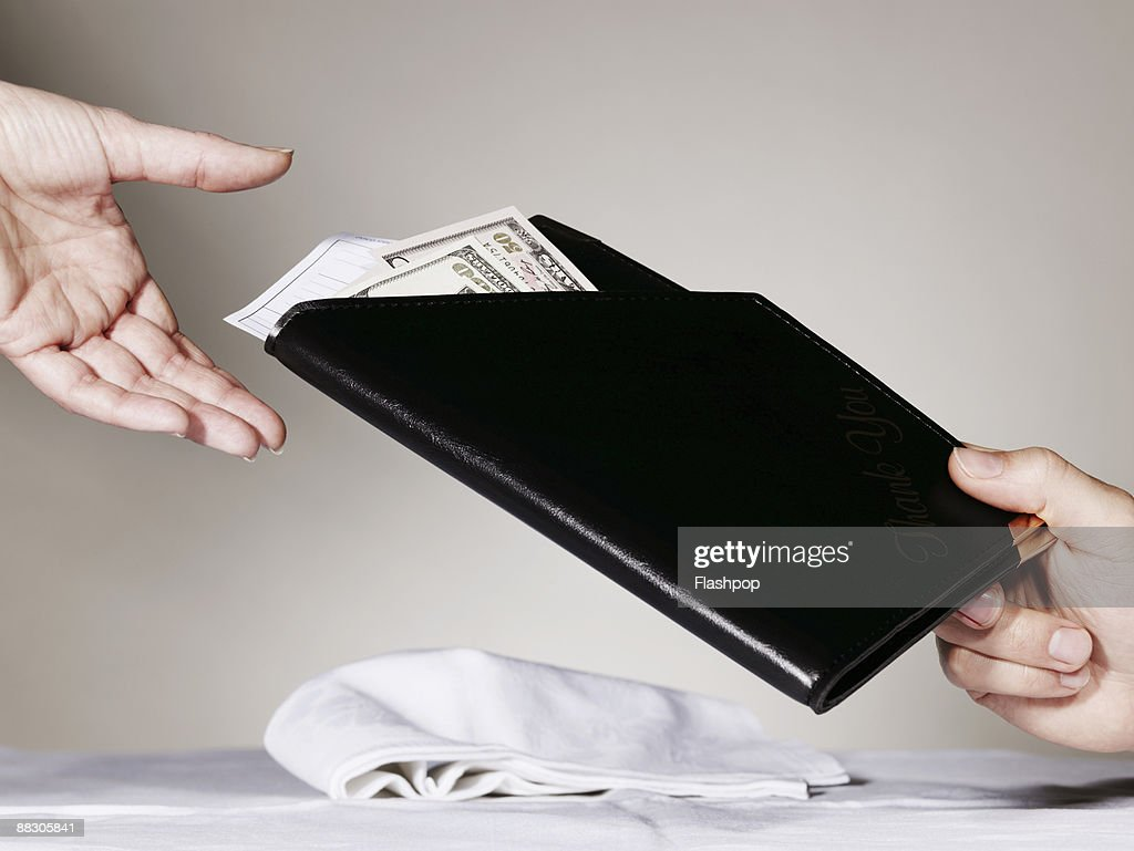 Person paying waiter for restaurant bill