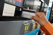 Person paying with credit card at gas pump, motion blur