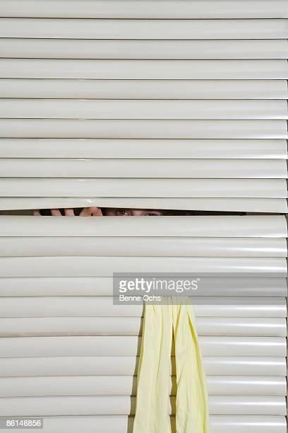 A person peeking through window blinds