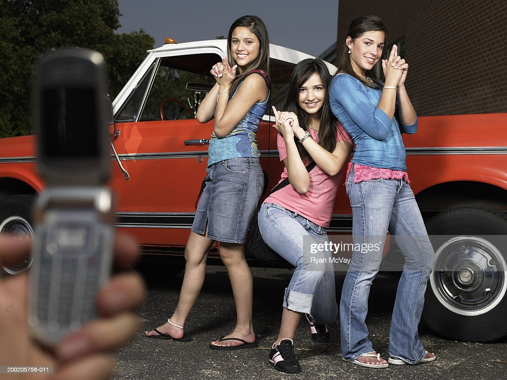 Person photographing three teenage girls (14-16) beside pick-up truck