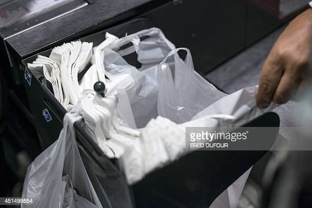 A person picks up a plastic bag on June 30 2014 in a supermarket in Paris A governmental amendment added to the biodiversity bill on June 25 aims for...