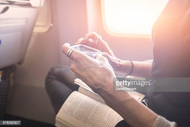 Person playing game on smartphone on board airplane