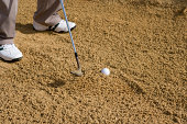 Person playing golf in sandy bunker, low section