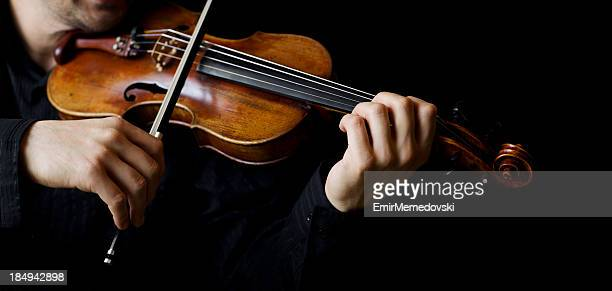 A person playing the violin showing hands holding the bow