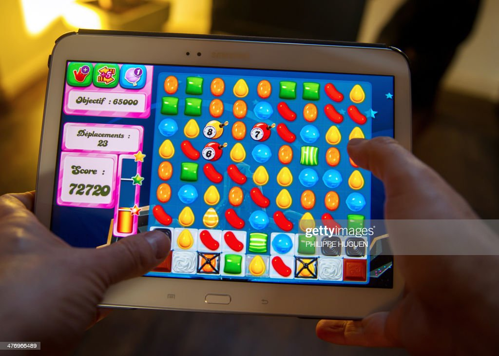 A person plays on his tablet with Candy Crush Saga games developed by British King Digital Entertainment, on March 6, 2014, in Lille, northern France. The game is free, but players can pay for in-app extras to help them pass up through its more than 500 levels. Millions of commuters, teenagers -- even pensioners -- clock in daily to test their skills at the game, which involves lining up tiny pieces of colored sweets to make them vanish from the screen of their computer or mobile phone. HUGUEN
