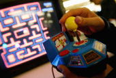 A person plays the new Ms PacMan game by JAKKS Pacific Inc at the Toy Industry Association Toy Wishes Holiday Preview show October 5 2004 in New York...