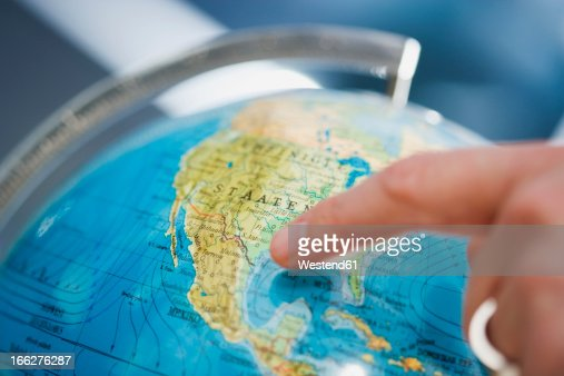 Person pointing at globe