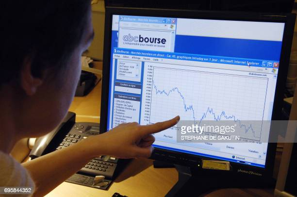 A person poses as she consults a website showing the graph of Paris CAC 40 stock market 21 January 2008 in Paris Paris stock market index closed 683...