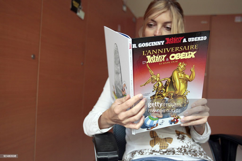 A person poses reading Asterix last comic book by late writer Rene Goscinny and illustrator Albert Uderzo 'L'anniversaire d'Astérix et Obélix, le livre d'or' (Asterix and Obelix birthday, the golden book), on October 22, 2009 in Paris. The album, marking the 50th anniversary of the character's first appearance in 1959, is released today in 15 countries, with three millions exemplaries, including 1,1 million for France. AFP PHOTO / FRANCOIS GUILLOT